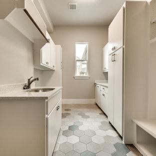 Klassisk inredning av en stor flerfärgade parallell flerfärgat tvättstuga enbart för tvätt, med en undermonterad diskho, släta luckor, vita skåp, bänkskiva i terrazo, beige väggar, klinkergolv i keramik, en tvättmaskin och torktumlare bredvid varandra och flerfärgat golv