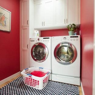 Idéer för en mellanstor modern linjär tvättstuga enbart för tvätt, med skåp i shakerstil, vita skåp, röda väggar, ljust trägolv och en tvättmaskin och torktumlare bredvid varandra