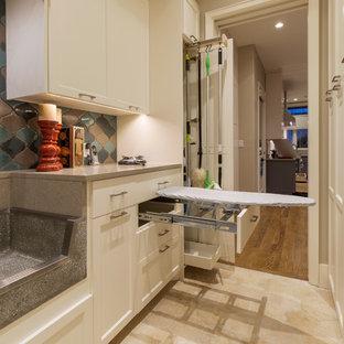 Foto på ett stort vintage u-format grovkök, med en allbänk, luckor med infälld panel, vita skåp, bänkskiva i kvarts, travertin golv, en tvättmaskin och torktumlare bredvid varandra och grå väggar