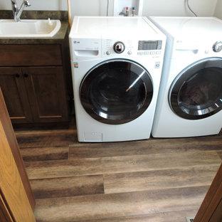 Inredning av en klassisk liten gröna parallell grönt tvättstuga enbart för tvätt, med en allbänk, luckor med infälld panel, skåp i mörkt trä, laminatbänkskiva, grönt stänkskydd, vita väggar, vinylgolv, en tvättmaskin och torktumlare bredvid varandra och brunt golv