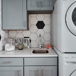 Immagine di una piccola sala lavanderia chic con lavello sottopiano, ante in stile shaker, ante blu, top in superficie solida, pareti bianche, pavimento con piastrelle in ceramica, lavatrice e asciugatrice a colonna, pavimento nero e top bianco
