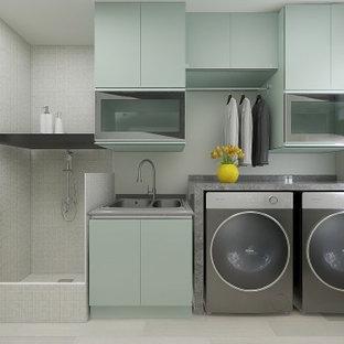 Idéer för ett litet modernt grå linjärt grovkök, med en dubbel diskho, luckor med glaspanel, gröna skåp, granitbänkskiva, grå väggar, klinkergolv i keramik, en tvättmaskin och torktumlare bredvid varandra och grått golv