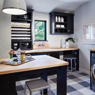 Immagine di una lavanderia multiuso mediterranea di medie dimensioni con lavello da incasso, nessun'anta, ante nere, top in legno, pareti grigie, lavatrice e asciugatrice affiancate, pavimento in linoleum e pavimento grigio