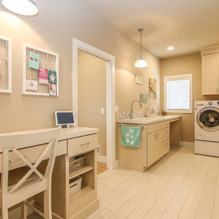Large beach style galley utility room in Other with a built-in sink, recessed-panel cabinets, beige cabinets, beige walls, light hardwood flooring, a side by side washer and dryer and beige floors.