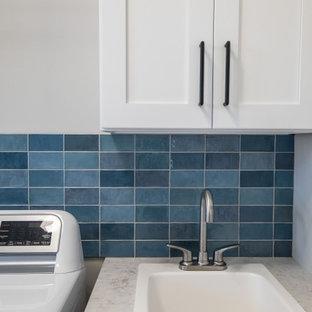 Exempel på en modern l-formad tvättstuga, med en nedsänkt diskho, skåp i shakerstil, vita skåp, laminatbänkskiva, blått stänkskydd, stänkskydd i keramik, grå väggar, vinylgolv, en tvättmaskin och torktumlare bredvid varandra och grått golv