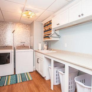Immagine di una sala lavanderia costiera di medie dimensioni con lavello a vasca singola, ante in stile shaker, ante bianche, top in laminato, pareti blu, pavimento in linoleum e lavatrice e asciugatrice affiancate
