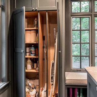 Idées déco pour une grand buanderie scandinave multi-usage avec des portes de placard grises, un plan de travail en quartz modifié, un mur gris, un sol en bois brun, des machines côte à côte et un placard avec porte à panneau encastré.