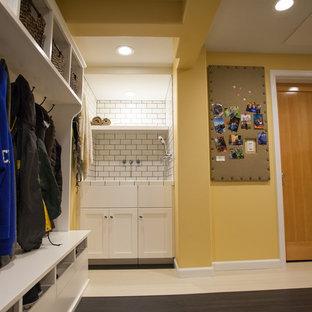 Foto på ett stort vintage l-format grovkök, med en integrerad diskho, skåp i shakerstil, vita skåp, laminatbänkskiva, gula väggar, linoleumgolv och en tvättmaskin och torktumlare bredvid varandra