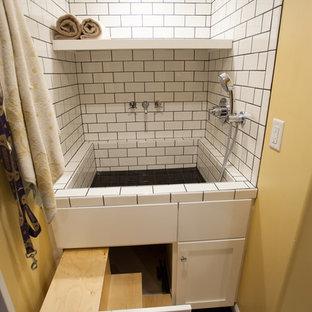 Klassisk inredning av ett stort grovkök, med en integrerad diskho, skåp i shakerstil, vita skåp, laminatbänkskiva, gula väggar, linoleumgolv och en tvättmaskin och torktumlare bredvid varandra