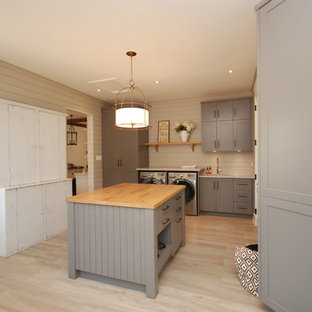 Exempel på ett stort klassiskt grovkök, med en undermonterad diskho, skåp i shakerstil, grå skåp, träbänkskiva, grå väggar, klinkergolv i porslin och en tvättmaskin och torktumlare bredvid varandra
