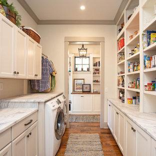 Inspiration för ett lantligt grå parallellt grått grovkök, med luckor med infälld panel, vita skåp, vita väggar, mellanmörkt trägolv, en tvättmaskin och torktumlare bredvid varandra och brunt golv