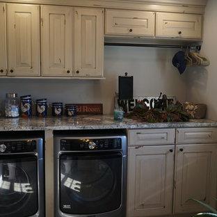 Immagine di una lavanderia multiuso country di medie dimensioni con lavello sottopiano, ante con bugna sagomata, ante con finitura invecchiata, top in granito, pareti grigie, pavimento in gres porcellanato e lavatrice e asciugatrice affiancate