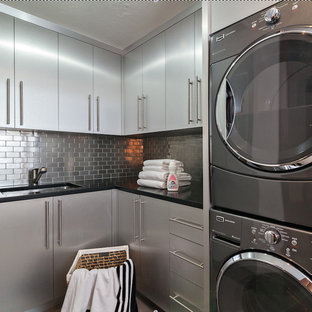 Inspiration for a medium sized modern l-shaped separated utility room in Miami with a submerged sink, flat-panel cabinets, grey cabinets, granite worktops, grey walls, travertine flooring, a stacked washer and dryer, beige floors and black worktops.