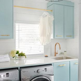 Idéer för vintage linjära tvättstugor enbart för tvätt, med en undermonterad diskho, blå skåp, vita väggar och en tvättmaskin och torktumlare bredvid varandra