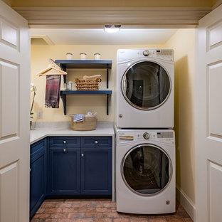 Idee per una piccola sala lavanderia classica con lavello sottopiano, ante con riquadro incassato, ante blu, top in quarzo composito, pareti gialle, pavimento in mattoni, lavatrice e asciugatrice a colonna, pavimento rosso e top grigio