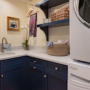 Bild på en liten vintage grå l-formad grått tvättstuga enbart för tvätt, med en undermonterad diskho, luckor med infälld panel, blå skåp, bänkskiva i kvarts, gula väggar, tegelgolv, en tvättpelare och rött golv