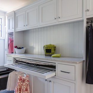 This is an example of a transitional galley dedicated laundry room in Raleigh with recessed-panel cabinets, white cabinets, granite benchtops, white walls, light hardwood floors and a side-by-side washer and dryer.