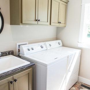Idéer för att renovera en mellanstor lantlig parallell tvättstuga enbart för tvätt, med en nedsänkt diskho, släta luckor, gröna skåp, laminatbänkskiva, grå väggar, tegelgolv, en tvättmaskin och torktumlare bredvid varandra och flerfärgat golv