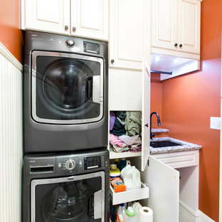 Foto di una lavanderia multiuso classica di medie dimensioni con lavello sottopiano, ante con bugna sagomata, ante bianche, top in granito, pareti arancioni, pavimento con piastrelle in ceramica e lavatrice e asciugatrice a colonna