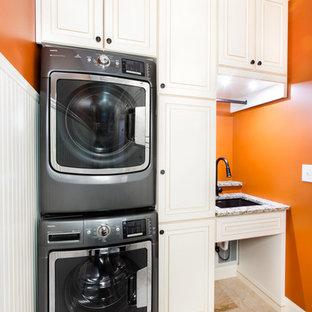 Idéer för att renovera en liten vintage tvättstuga, med en undermonterad diskho, luckor med upphöjd panel, vita skåp, granitbänkskiva, orange väggar, klinkergolv i keramik och en tvättpelare