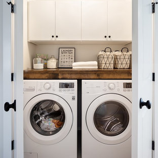 This is an example of a small country laundry cupboard in Vancouver with flat-panel cabinets, white cabinets, wood benchtops, white walls, porcelain floors, a side-by-side washer and dryer and grey floor.