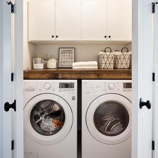 Foto di un piccolo ripostiglio-lavanderia country con ante lisce, ante bianche, top in legno, pareti bianche, pavimento in gres porcellanato, lavatrice e asciugatrice affiancate e pavimento grigio