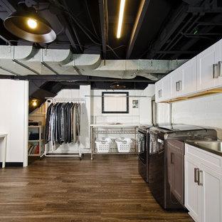 Bild på ett mellanstort industriellt grovkök, med en integrerad diskho, skåp i shakerstil, vita skåp, vita väggar, laminatgolv, en tvättmaskin och torktumlare bredvid varandra och brunt golv