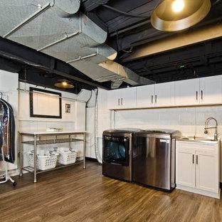 Foto di una lavanderia multiuso industriale di medie dimensioni con ante in stile shaker, ante bianche, pareti bianche, pavimento in laminato, lavatrice e asciugatrice affiancate, pavimento marrone e lavello da incasso