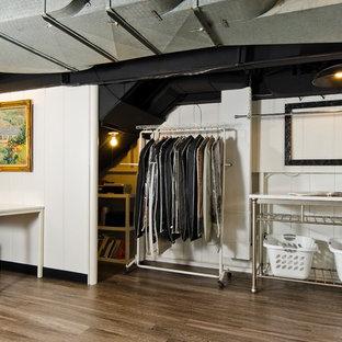 Inspiration för ett mellanstort industriellt grovkök, med en integrerad diskho, skåp i shakerstil, vita skåp, vita väggar, laminatgolv, en tvättmaskin och torktumlare bredvid varandra och brunt golv