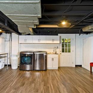 Inredning av ett industriellt mellanstort grovkök, med en integrerad diskho, skåp i shakerstil, vita skåp, vita väggar, laminatgolv, en tvättmaskin och torktumlare bredvid varandra och brunt golv
