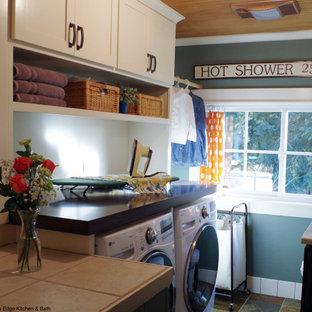 Immagine di una piccola lavanderia multiuso american style con lavello a vasca singola, ante in stile shaker, ante bianche, top in legno, pareti verdi, pavimento in ardesia, lavatrice e asciugatrice affiancate, top marrone e soffitto in legno