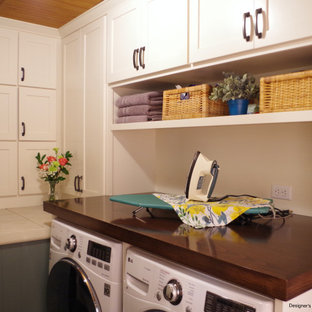 This is an example of a small arts and crafts single-wall utility room in Portland with a single-bowl sink, shaker cabinets, white cabinets, wood benchtops, green walls, slate floors, a side-by-side washer and dryer, brown benchtop and wood.