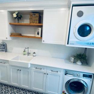 Idéer för att renovera en stor maritim vita parallell vitt tvättstuga enbart för tvätt, med en rustik diskho, skåp i shakerstil, vita skåp, bänkskiva i kvarts, vitt stänkskydd, stänkskydd i tunnelbanekakel, vita väggar, klinkergolv i keramik och svart golv