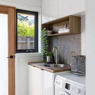 Idéer för en liten modern linjär tvättstuga, med öppna hyllor och gula väggar