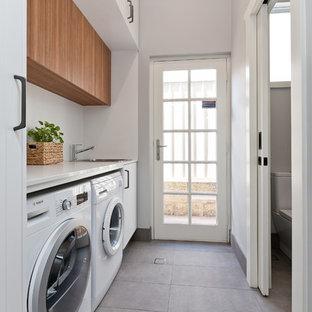 Immagine di una piccola sala lavanderia contemporanea con lavello da incasso, ante bianche, top in quarzo composito, pareti grigie, pavimento in gres porcellanato, lavatrice e asciugatrice affiancate, pavimento grigio, top bianco e ante lisce