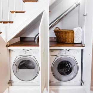 Idee per un piccolo ripostiglio-lavanderia classico con ante in stile shaker, ante bianche, top in legno, pavimento in legno massello medio, lavatrice e asciugatrice affiancate, pavimento marrone e top marrone