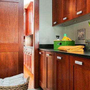 Foto di una sala lavanderia tradizionale di medie dimensioni con lavello sottopiano, ante con riquadro incassato, ante in legno scuro e lavatrice e asciugatrice affiancate