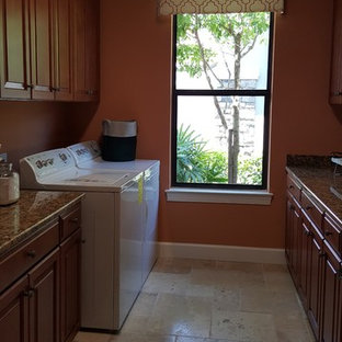 Photo of a large traditional galley separated utility room in Miami with raised-panel cabinets, medium wood cabinets, granite worktops, orange walls, travertine flooring, a side by side washer and dryer and a built-in sink.