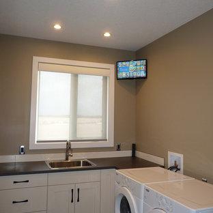 Ispirazione per una piccola sala lavanderia minimalista con lavello a vasca singola, ante in stile shaker, ante bianche, top in laminato, pareti marroni, pavimento in linoleum, lavatrice e asciugatrice affiancate, pavimento marrone e top marrone