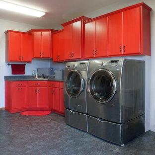 Ispirazione per una lavanderia minimalista con lavello da incasso, ante lisce, ante rosse, top in laminato, pareti blu e lavatrice e asciugatrice affiancate