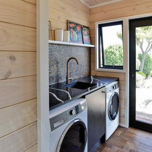 Inspiration for a small rural single-wall utility room in Other with a submerged sink, flat-panel cabinets, black cabinets, engineered stone countertops, dark hardwood flooring, a side by side washer and dryer, brown floors, black worktops and beige walls.