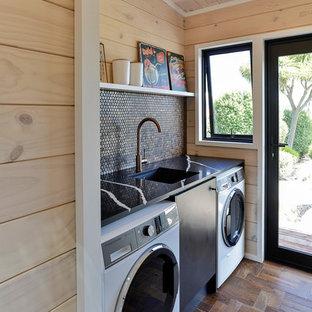 Idéer för att renovera en liten lantlig svarta linjär svart tvättstuga, med en undermonterad diskho, släta luckor, svarta skåp, bänkskiva i kvarts, mörkt trägolv, en tvättmaskin och torktumlare bredvid varandra, brunt golv och beige väggar