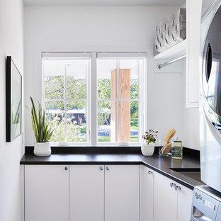 Стильный дизайн: маленькая отдельная, угловая прачечная в скандинавском стиле с врезной раковиной, плоскими фасадами, белыми фасадами, белыми стенами, с сушильной машиной на стиральной машине, столешницей из ламината, полом из керамогранита и бежевым полом - последний тренд