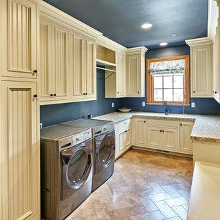 Bild på ett mycket stort vintage u-format grovkök, med en undermonterad diskho, luckor med infälld panel, vita skåp, granitbänkskiva, blå väggar, travertin golv och en tvättmaskin och torktumlare bredvid varandra