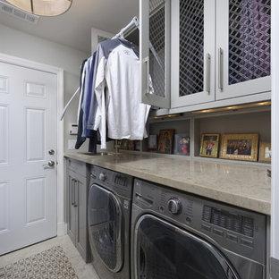 Inredning av ett klassiskt mellanstort grå parallellt grått grovkök, med en undermonterad diskho, skåp i shakerstil, grå skåp, bänkskiva i kalksten, grå väggar, marmorgolv, en tvättmaskin och torktumlare bredvid varandra och grått golv
