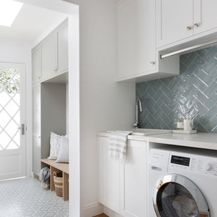 Photo of a beach style utility room in Gold Coast - Tweed with shaker cabinets, white cabinets, white walls, a side-by-side washer and dryer, grey floor, white benchtop, a drop-in sink, quartz benchtops and porcelain floors.