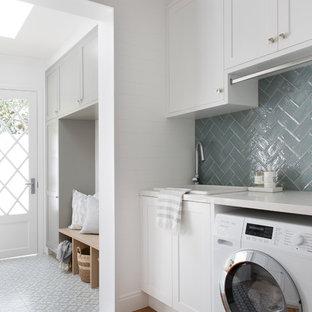 Maritim inredning av ett vit vitt grovkök, med skåp i shakerstil, vita skåp, vita väggar, en tvättmaskin och torktumlare bredvid varandra, grått golv, en nedsänkt diskho, bänkskiva i kvarts och klinkergolv i porslin