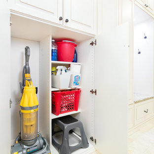Small elegant ceramic floor laundry room photo in Chicago with raised-panel cabinets, white cabinets, granite countertops and a stacked washer/dryer