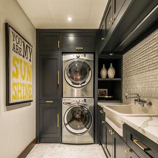 Immagine di una lavanderia tradizionale di medie dimensioni con lavello stile country, ante in stile shaker, top in marmo, pareti bianche, pavimento in marmo, lavatrice e asciugatrice a colonna, pavimento bianco e ante nere