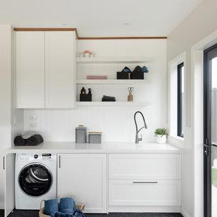 Cette image montre une buanderie linéaire design multi-usage et de taille moyenne avec un évier encastré, un placard à porte shaker, des portes de placard blanches, un plan de travail en quartz, une crédence blanche, une crédence en bois, un mur blanc, moquette, le lave-linge et le sèche-linge forment un seul appareil électroménager, un sol gris, un plan de travail blanc, un plafond voûté et du lambris de bois.